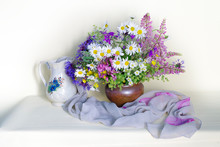 Still Life With Daisies In A Clay Vase On A White Background