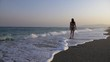young woman walking on seashore of rough sea - slow motion