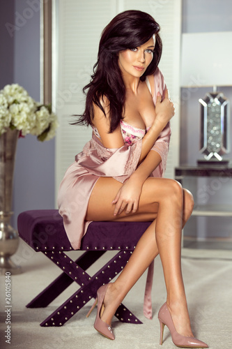 Sexy brunette woman in sensual lingerie sitting on a purple chair Canvas Print
