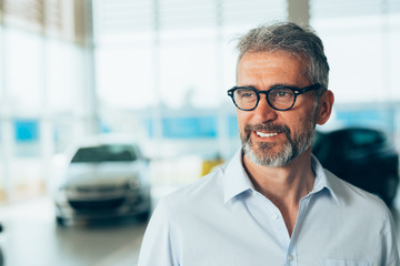 portrait of bearded sell agent in car dealers showroom