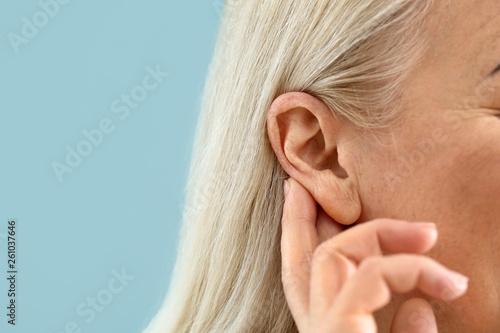 Fotografering Mature woman with hearing problem on color background, closeup