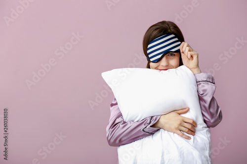 Photo Sleepy woman with mask and pillow on color background
