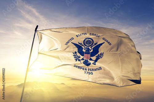 United States Coast Guard flag waving on the top sunrise mist fog