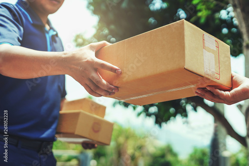 Obraz Delivery man delivering holding parcel box to customer - fototapety do salonu