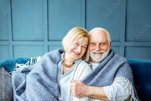 Photo Portrait of a lovely senior couple feeling cozy and warm, sitting wrapped with p