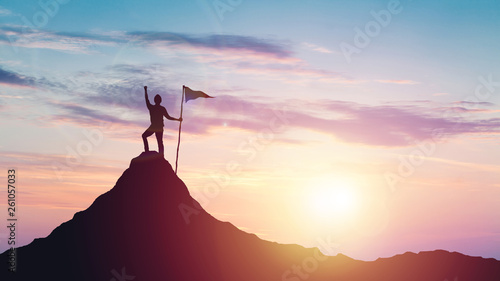 Платно Man with flag celebrates victory on top of a mountain at sunset