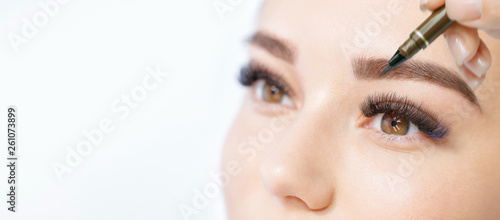 Beautiful young girl with long eyelashes tweezing her eyebrows in a beauty salon Fototapet