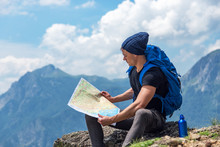 Male Handsome Hiker Using Map To Navigate In Nature