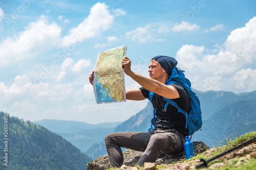 Canvas Prints Blue Male handsome hiker using map to navigate in nature