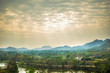 cloudy with sunlight rays shine on land scape of country and blue mountain.