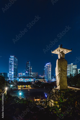 Poster Historisch mon. buddha statue at bongeunsa temple with cityscape of seoul at nig