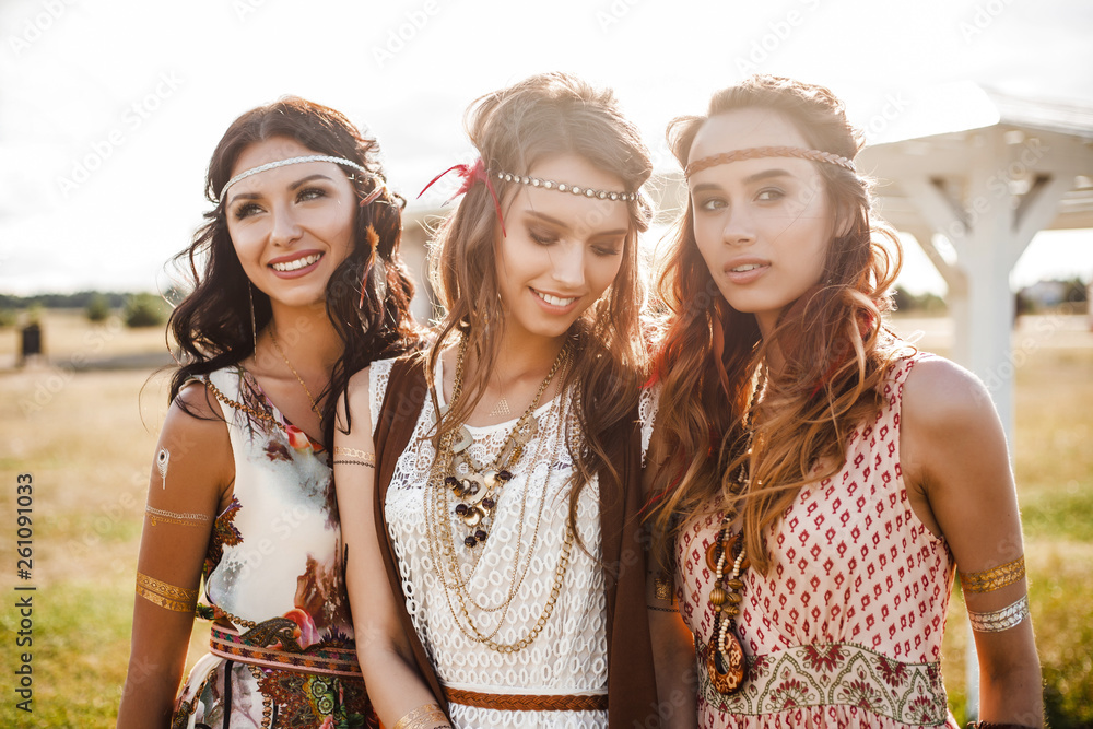 Fototapety, obrazy: Three cute beautiful hippie girl in the setting sun, outdoors, the best of friends smiling and having fun, makeup, long hair, feathers in their hair, bracelets, flash tattoo, indie, Bohemia boho style