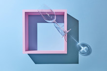 A Glass On A Pink Wooden Frame Is Presented On A Blue Background.