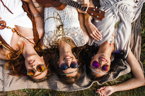 Foto  Three cute hippie girl lying on the plaid outdoors, best friends having fun and
