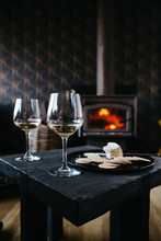Two Glasses Of White Wine In Front Of A Fire