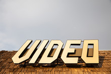 Old Video Sign Atop An Abandoned Storefront Roof In USA