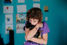 Girl Holds Kitten Tight While Kissing Its Back