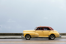Yellow Shiny Retro Car With White Roof Riding On Street Of Tropi