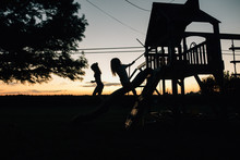 Two Girls Playing In Tree House During Sunset