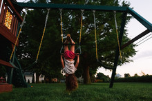 Little Girl Hanging Upside Down On Playset