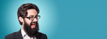 Funny Handsome Businessman Looking At Camera And Winking, Panoramic Image Over Blue Background
