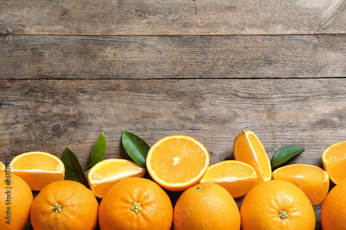 Flat lay composition with ripe oranges and space for text on wooden background