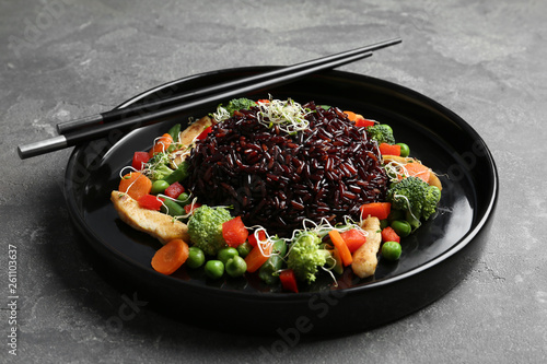 Fototapeta Plate of cooked brown rice with vegetables and chopsticks on table obraz