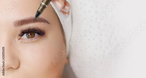 Obraz Beautiful young girl with long eyelashes tweezing her eyebrows in a beauty salon. Woman doing eyebrow permanent makeup correction . Microblading brow. - fototapety do salonu