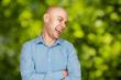 Portrait bald man laughing mockingly at something or someone on green bokeh background
