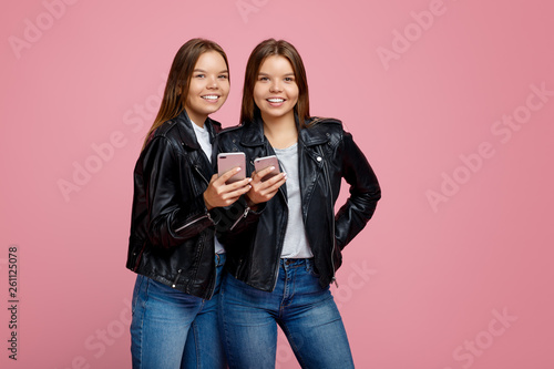 Nice two young twin sisters with bright smile in leather jackets use smartphone over pink background Wallpaper Mural