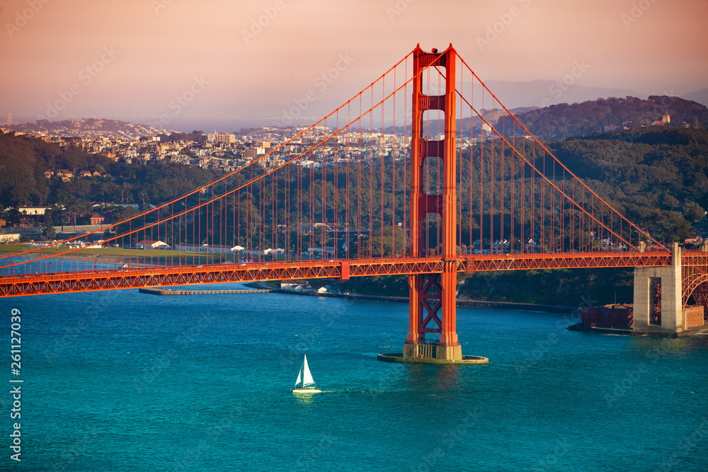 Fototapeta Yacht passing under Golden Gate Bridge at sunset