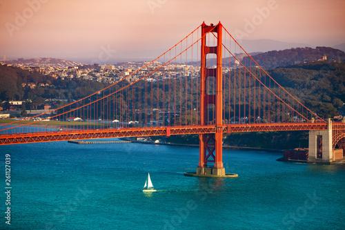 Fotografie, Tablou Yacht passing under Golden Gate Bridge at sunset
