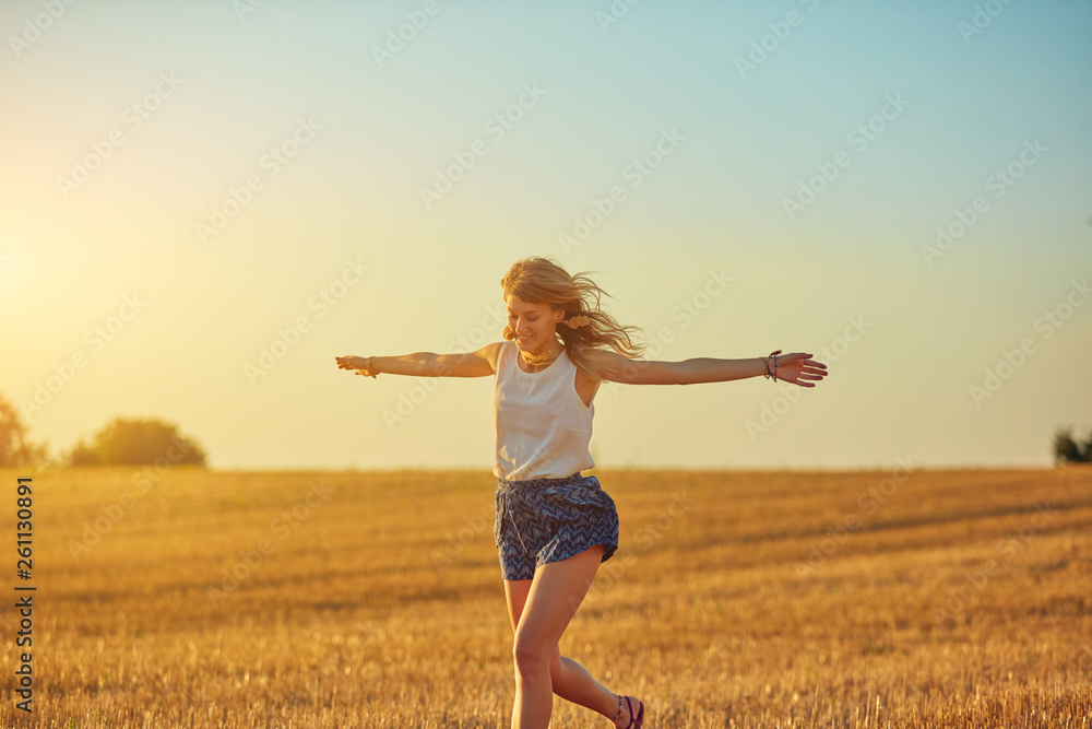 Fototapeta Cute young woman jumping in a wheat field.