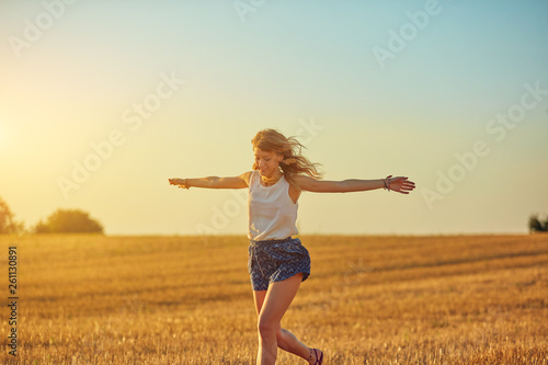 Fotografiet  Cute young woman jumping in a wheat field.