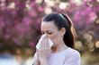 Leinwandbild Motiv Woman blowing nose because of spring pollen allergy