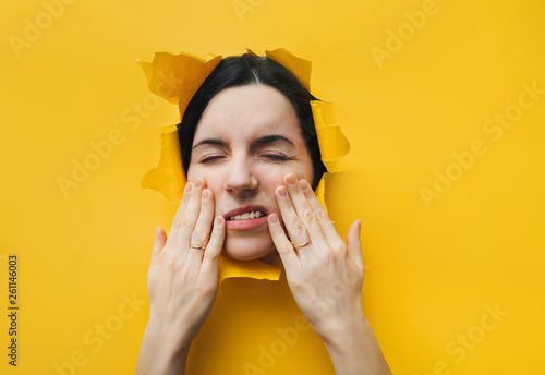 Fotografia  A young girl is having a toothache and holding her cheek with her hand