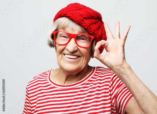 Obraz Lifestyle, emotion and people concept: Elderly happy woman showing ok - fototapety do salonu