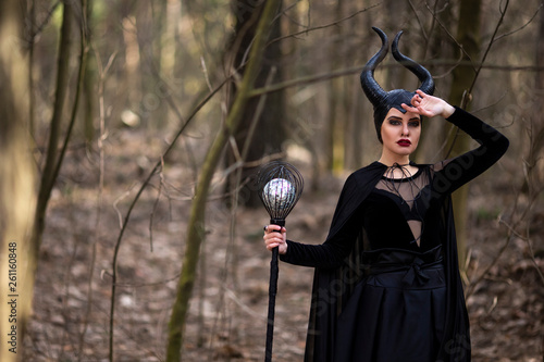 Fotografie, Obraz  Marvellous and Magical Maleficent Woman with Horns Posing in Spring Empty Forest with Crook