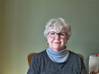 Senior woman with glasses looking at camera and smiling with confidence.