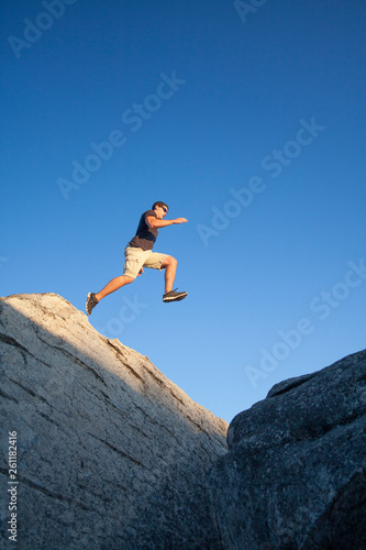 Fotografía  A young man outdoors leaping from one boulder to another in the Sierra Nevada Mountains of Northern California