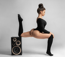 Beautiful Brunette Woman In Black Bodysuit Sits And Leans On A Music Speaker.