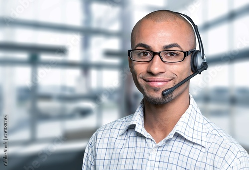 Fotografie, Obraz Portrait of a smiling man with headset working as a call center operator