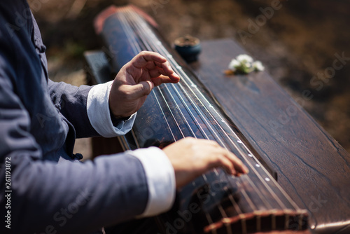 The man is playing the Guqin - 261193872