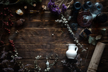 Various Dried Herbs And Bottles On A Brown Wooden Table. Herbal Medicine, Alternative Medicine Concept Background Or Witch Doctor.