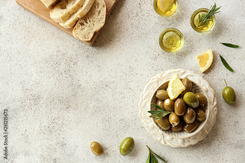Fotografiet Bowl with tasty olives and fresh bread on grey background