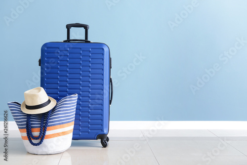 Fotografie, Obraz Packed suitcase and beach bag near color wall