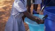 African school pupils wash their hands outside in a plastic dish with water poured from a jug before mealtime