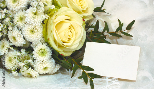 Fototapeta Bouquet of white and yellow flowers with an empty greeting card