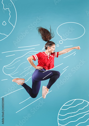 Obraz Hurry up to save the universe. Dreaming about cosmonaut profession or travel the cosmos. Young woman in drawing imaginary spacesuit against blue background. Concept of childhood and dreams. - fototapety do salonu
