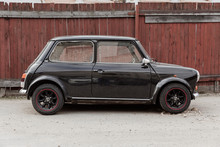Black Old Classic Mini Cuper. Street And Wooden Yard. Travel Photo 2019.